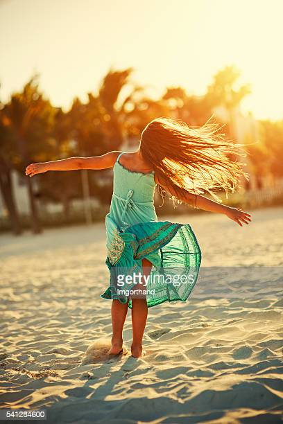 Little girl dancing on the beach.