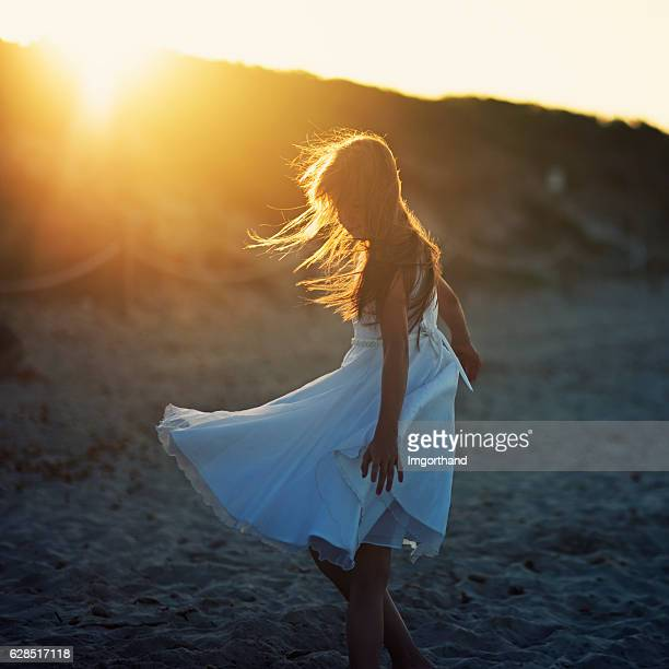 little girl dancing on the beach. - flare stack stock photos and pictures