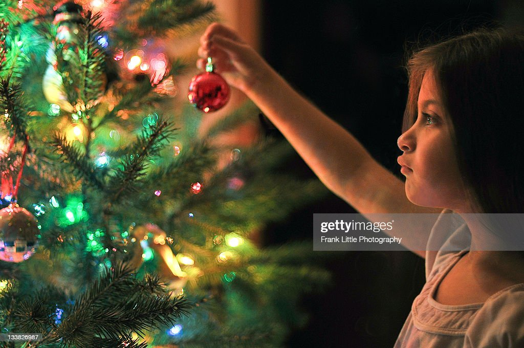 Little girl decorating beautiful Christmas tree : Stock Photo