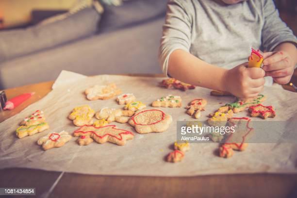 little girl decorating christmas cookies at home, hands close up - sugar baby imagens e fotografias de stock