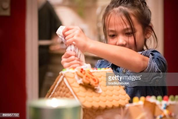 Little girl decorating Christmas gingerbread house