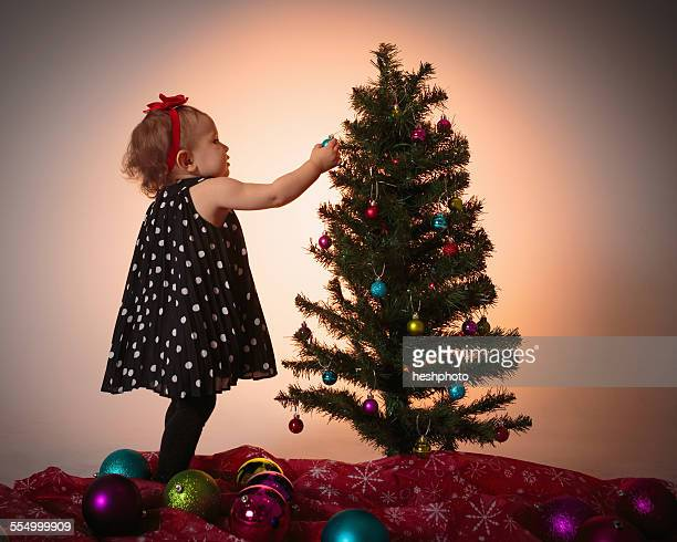 little girl decorating christmas tree - heshphoto stock pictures, royalty-free photos & images