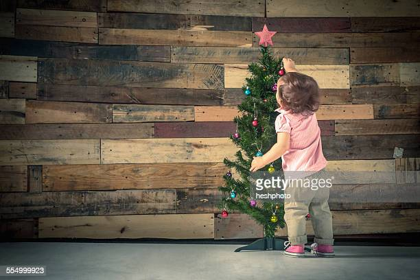 little girl decorating christmas tree - heshphoto photos et images de collection