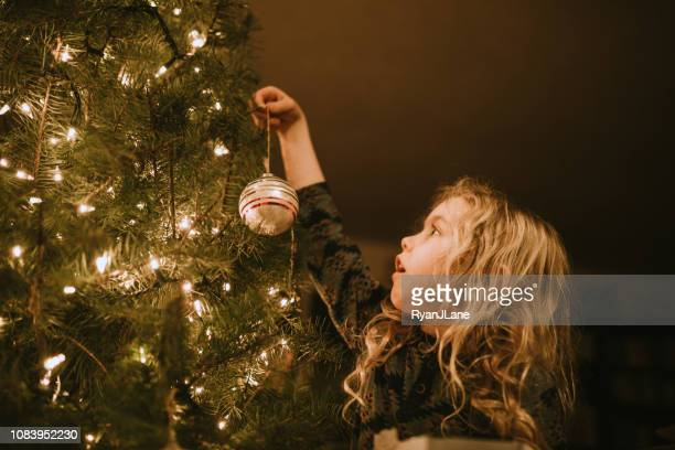 little girl decorating christmas tree with ornaments - ornato foto e immagini stock
