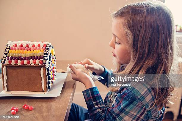 Little girl decorating gingerbread house with candy at home.
