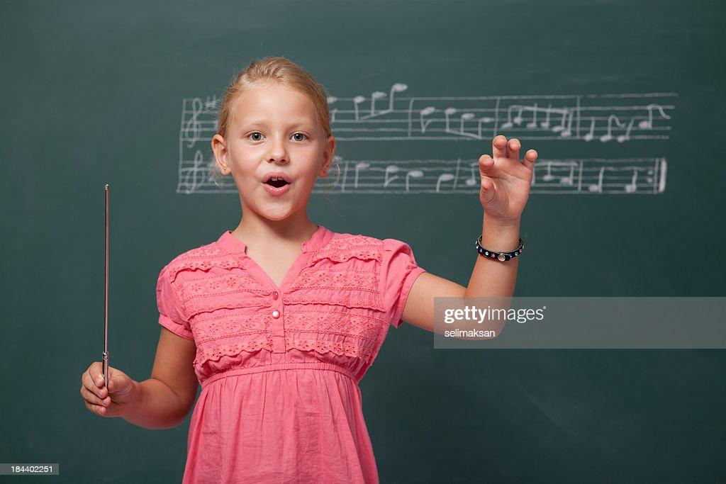 Kleines Mädchen Regeln Chorus für Folk vor der Tafel : Stock-Foto