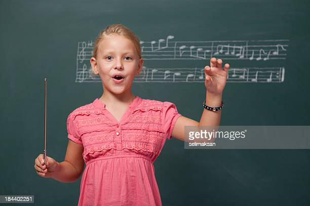 little girl directing chorus for folk music before blackboard - choir stock pictures, royalty-free photos & images