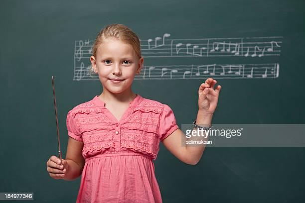 Little girl directing chorus for folk music before blackboard