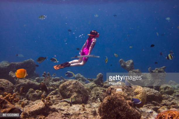 Little girl diving in a coral reef