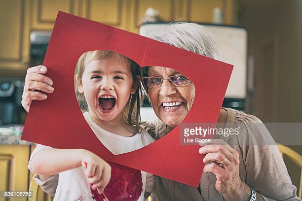 little girl doing bricolage with grandmother - valentine's day holiday stock pictures, royalty-free photos & images