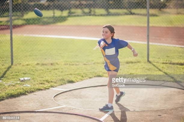 Little Girl Doing Discus Throwing In Athletics Club