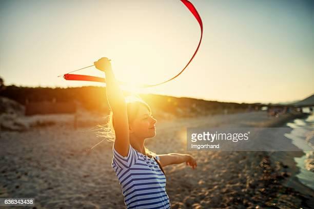 Little girl doing gymnastics on the beach.