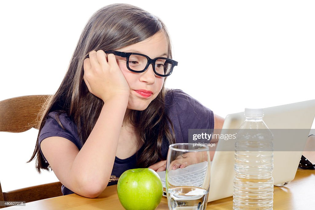 little girl doing her homework on her computer : Stock Photo