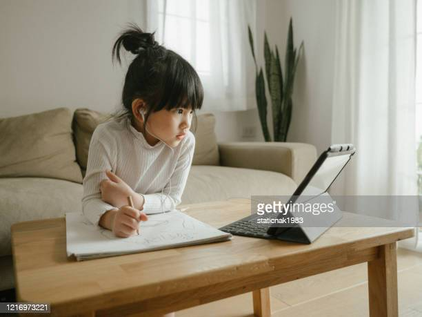 little girl doing her homework with digital tablet. - homeschool stock pictures, royalty-free photos & images
