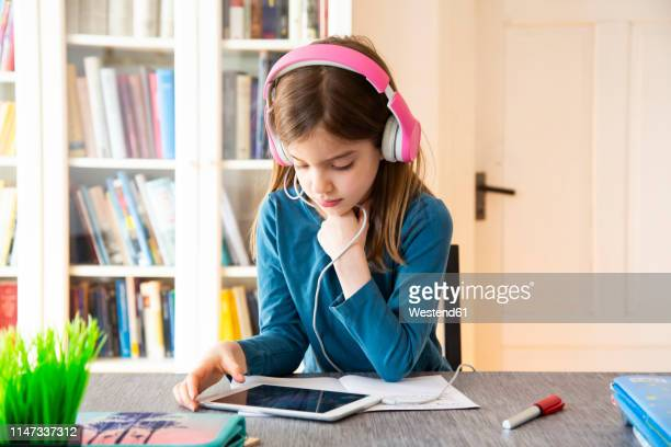 little girl doing homework with headphones and digital tablet - home schooling stock pictures, royalty-free photos & images