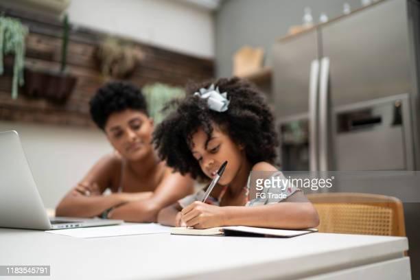 menina que faz trabalhos de casa com sua irmã - criança - fotografias e filmes do acervo