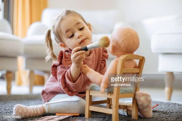 彼女の人形に化粧をしている小さな女の子 - 人形 ストックフォトと画像