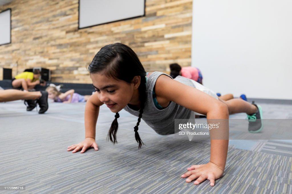 Little girl doing pushups in gym class : Stock Photo