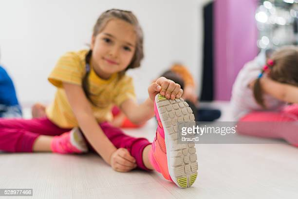 Little girl doing stretching exercises on a sports training.