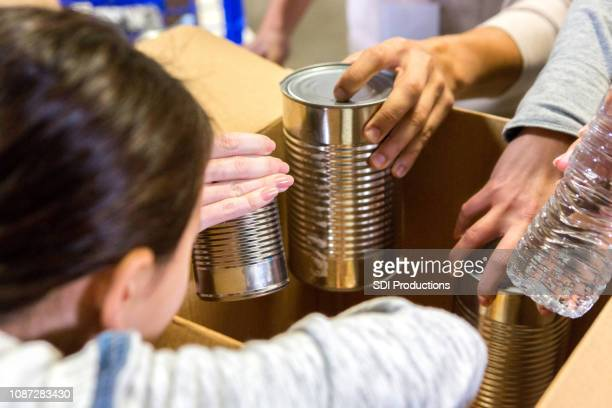little girl donates canned goods during food drive - food drive stock pictures, royalty-free photos & images