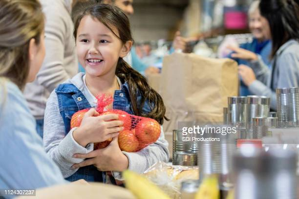 little girl donates food during food drive - food bank stock pictures, royalty-free photos & images