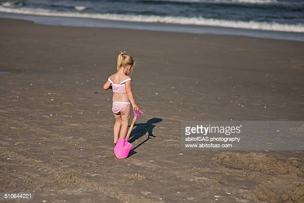 Little girl drags shovel over sand at beach