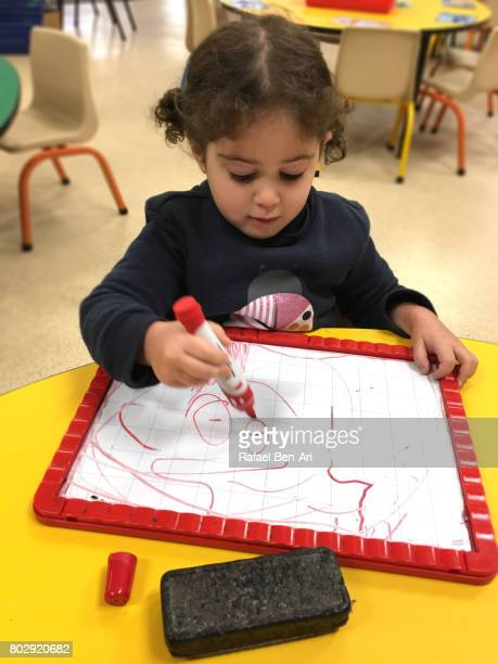 Little girl drawing a face on a white board