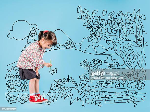 Little girl drawing a forest on blue background