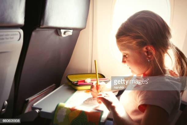 little girl drawing a picture during flight - colouring book stock photos and pictures