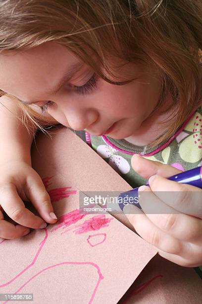 Little girl drawing and scribbling with pink felt-tipped pen