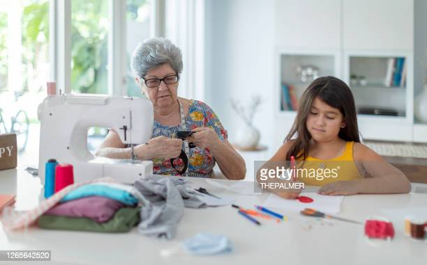 little girl drawing hearts while grandma sew mask for covid-19 - southwest stock pictures, royalty-free photos & images