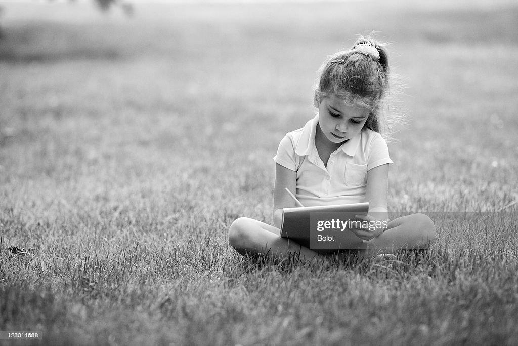Bambina disegno in un parco : Foto stock