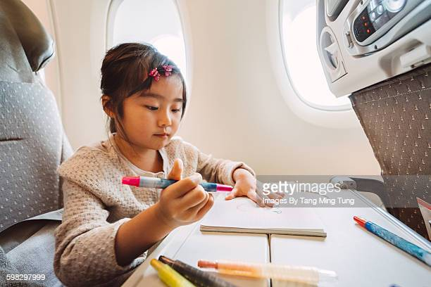 Little girl drawing in the aircraft cabin