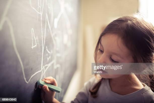 Little girl drawing on blackboard
