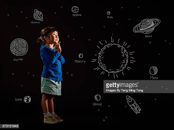 Little girl drawing planets on black background