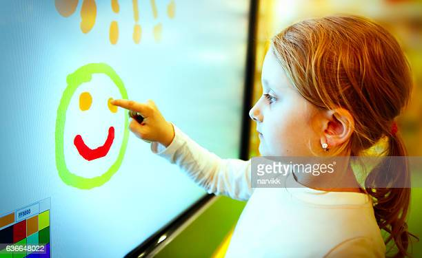 little girl drawing with finger on the touch screen - touch sensitive stock pictures, royalty-free photos & images