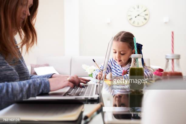Little girl drawing with pencil at table beside her mother typing on keyboard of laptop