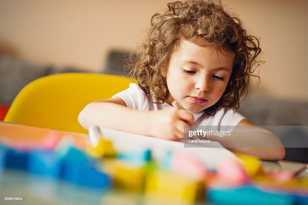 Little girl drawing with pencil : Stock Photo