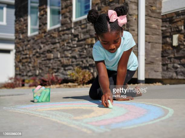 little girl drawing with sidewalk chalk - chalk stock pictures, royalty-free photos & images