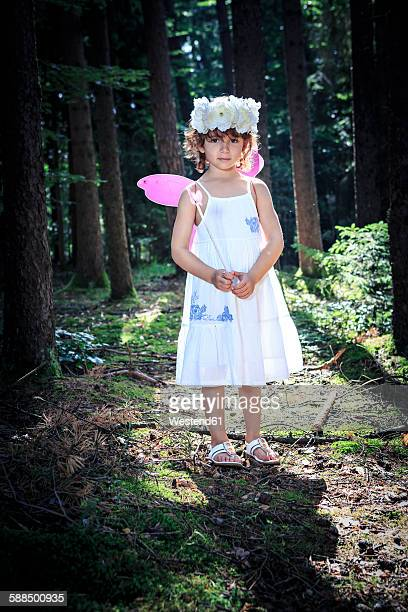 Little girl dressed as a fairy in the woods