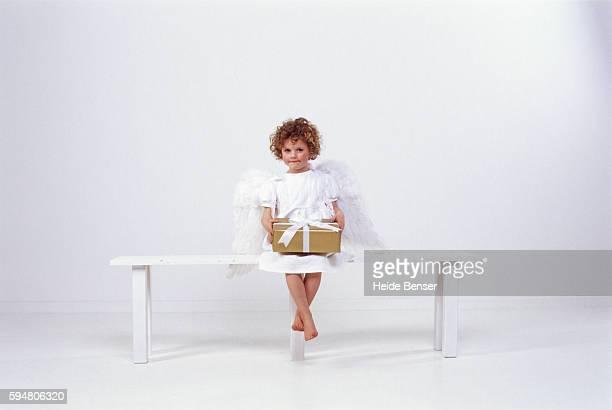 Little girl dressed as angel, holding present