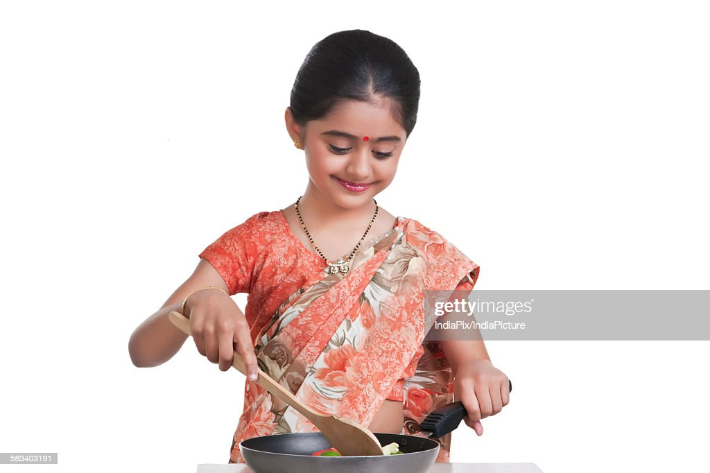 Little girl dressed as housewife cooking : Stock Photo