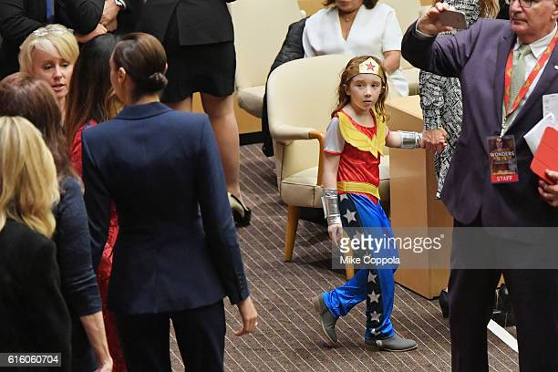 A little girl dressed in a Wonder Woman costume looks on at actors Gal Gadot and Lynda Carter as they pose for a picture at the Wonder Woman UN...