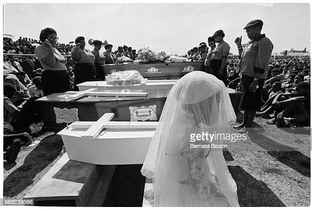 A little girl dressed in white garments is seated before people surrounding coffins at the funeral of nine people killed during the August 28...