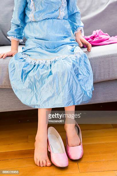 Little girl dressed up as a princess trying on ladys shoe, partial view