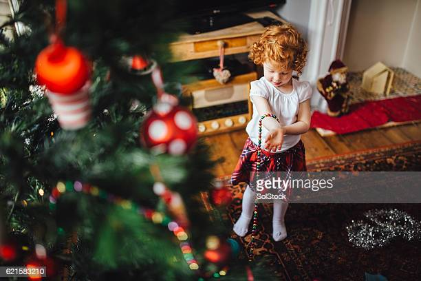 Little Girl dressing up in the  Christmas Decorations