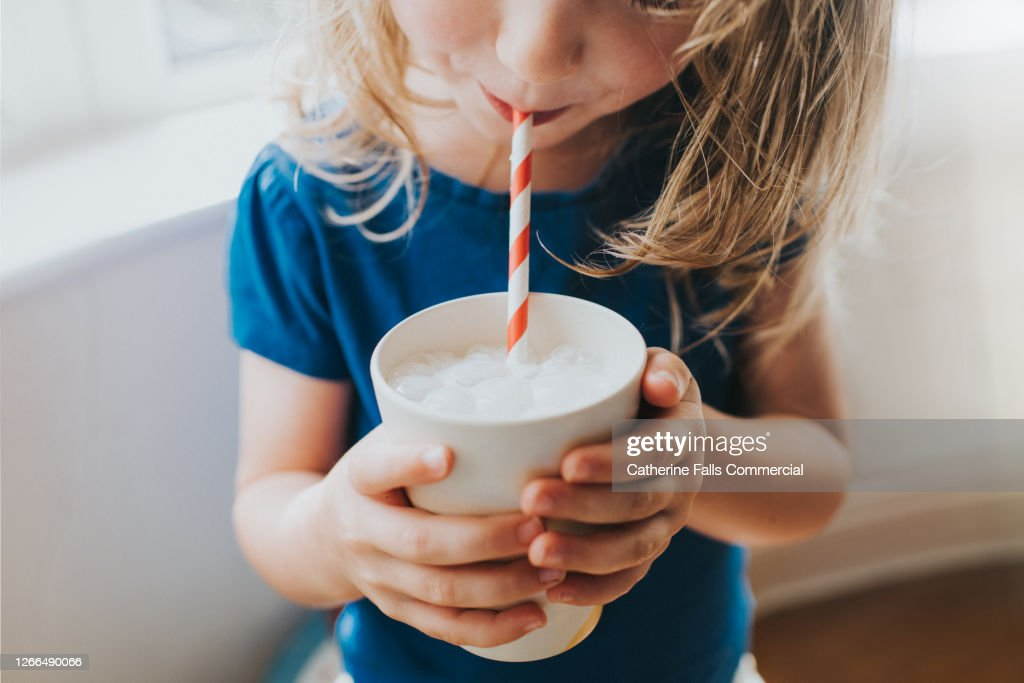 Little girl drinking a Cup of Milk with a Paper Straw : Stock Photo