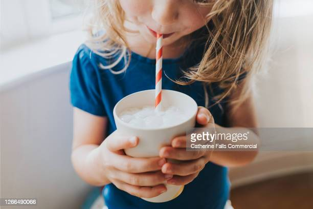 little girl drinking a cup of milk with a paper straw - drink stock pictures, royalty-free photos & images