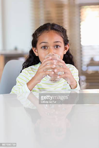 Little girl drinking a glass of water at home