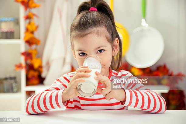 little girl drinking glass of milk - alleen één meisje stockfoto's en -beelden